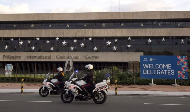 File picture shows policemen riding their motorcycles past the Philippine International Convention Center in Manila